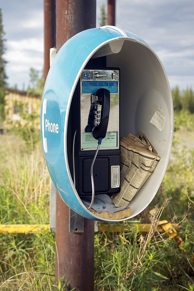Retro style Public telephone, with weather-worn telephone directories and a post-it note stuck to the inside.  Roadside amenity  in the Alaskan Interior. The Interior, Alaska, USA