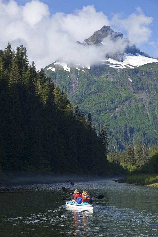 Kayaking in Red Bluff Bay on Baranof Island in Southeast Alaska, USA. Pacific Ocean. Kayak property release is DB051905. Model released numbers BM0807, JP0807, or DP0807.