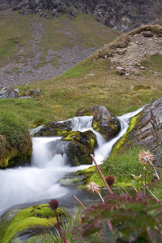 View of a small waterfall outside of Grytviken (Swedish for 'Pot Cove'), the principal settlement in the United Kingdom territory of South Georgia in the South Atlantic. It was so named by a 1902 Swedish surveyor who found old English try pots used to render seal oil at the site. It is the best harbour on the island, consisting of a bay (King Edward Cove) within a bay (Cumberland East Bay). The site is very sheltered, provides a substantial area of flat land suitable for building on, and has a good supply of fresh water. The settlement at Grytviken was established on November 16, 1904, by the Norwegian sea captain Carl Anton Larsen as a whaling station for his Compañía Argentina de Pesca (Argentine Fishing Company).