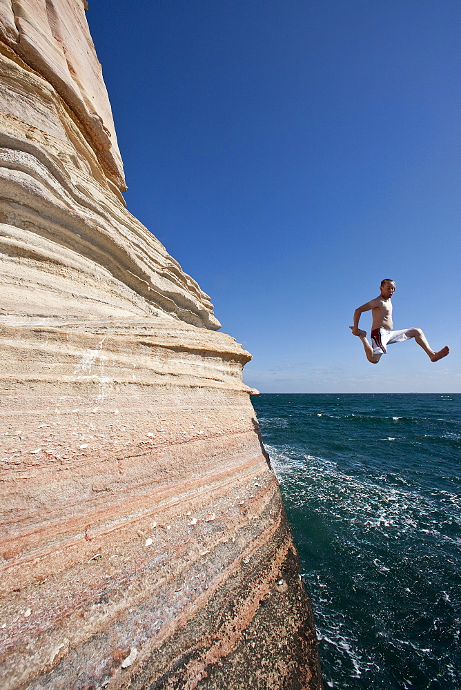 The Lindblad expedition ship National Geographic Sea Lion staff diving off the sandstone cliffs at Isla San Jose in the Gulf of California (Sea of Cortez) near the Baja Peninsula, Mexico. No model release is available for this image.