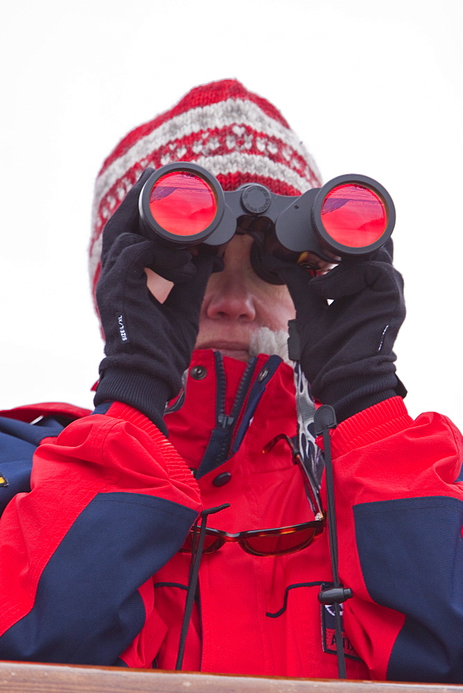 Guest from the Lindblad Expedition ship National Geographic Explorer scanning for polar bears around the Svalbard Archipelago in the summer months