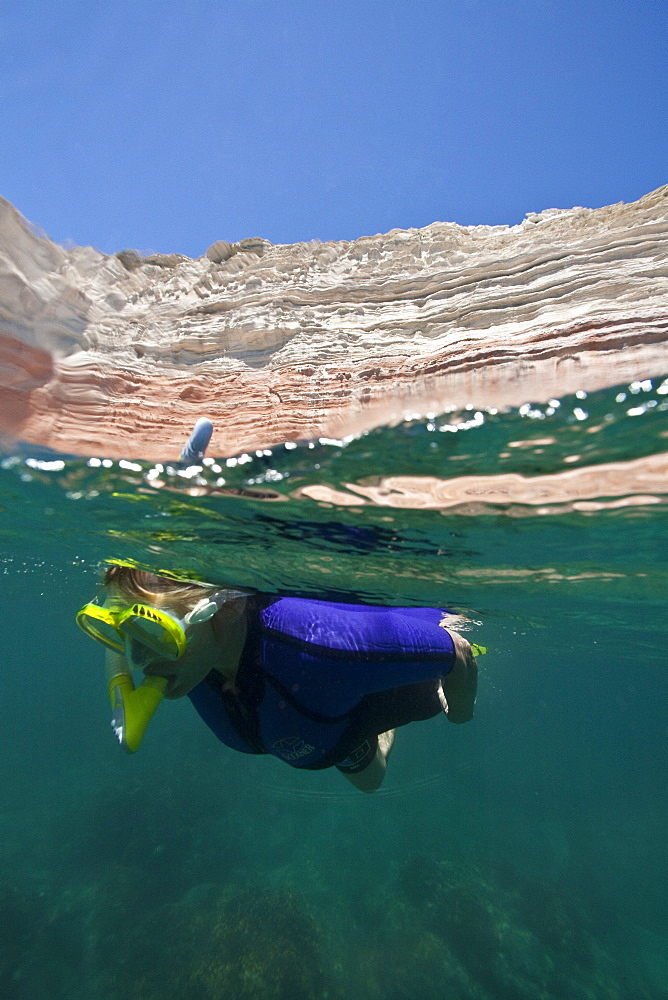 A snorkeler at Punta Colorado on Isla San Jose in the Gulf of California (Sea of Cortez), Baja California Sur, Mexico. MORE INFO A unique half above and half below the water look at the sandstone cliffs of this island.