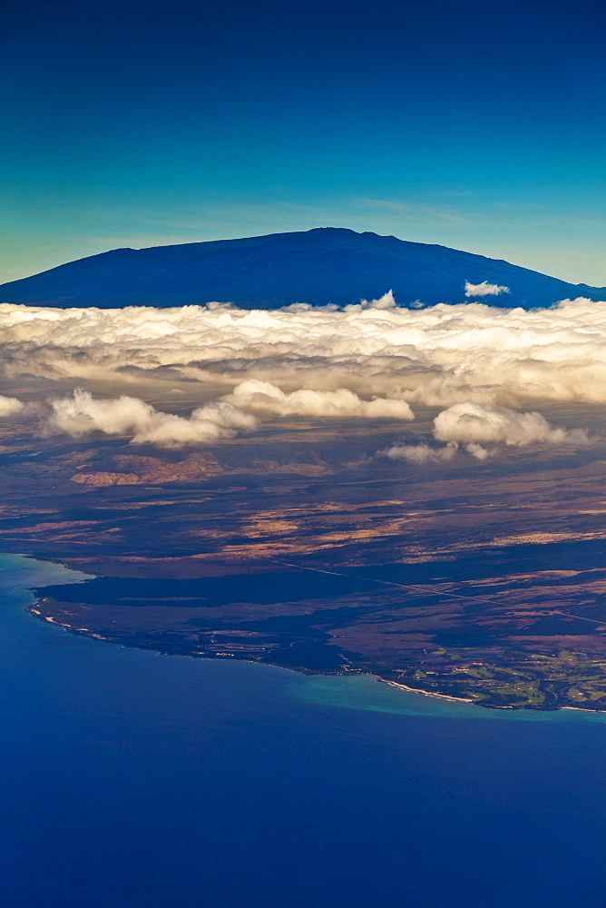 Mauna Kea, the tallest volcanic mountain in the chain of Hawaiian Islands, with its summit rising to the elevation of 13,796 ft (4,205 m) above sea level, observatories visible at summit, coastline of Kiholo Bay to Hualalai Resort below clouds, Big Island, Hawaii, USA
