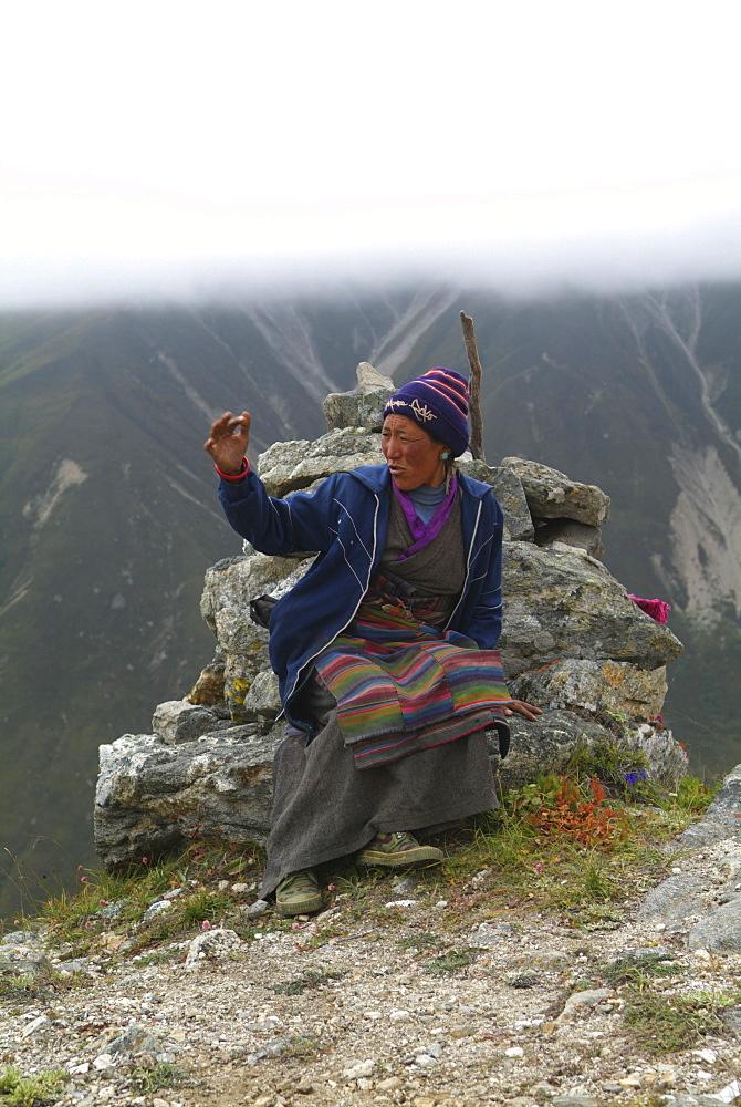 Tibetan Lady.  Mountain and Clouds.Traditional Dress,  Himalayas, Tibet. - 986-124