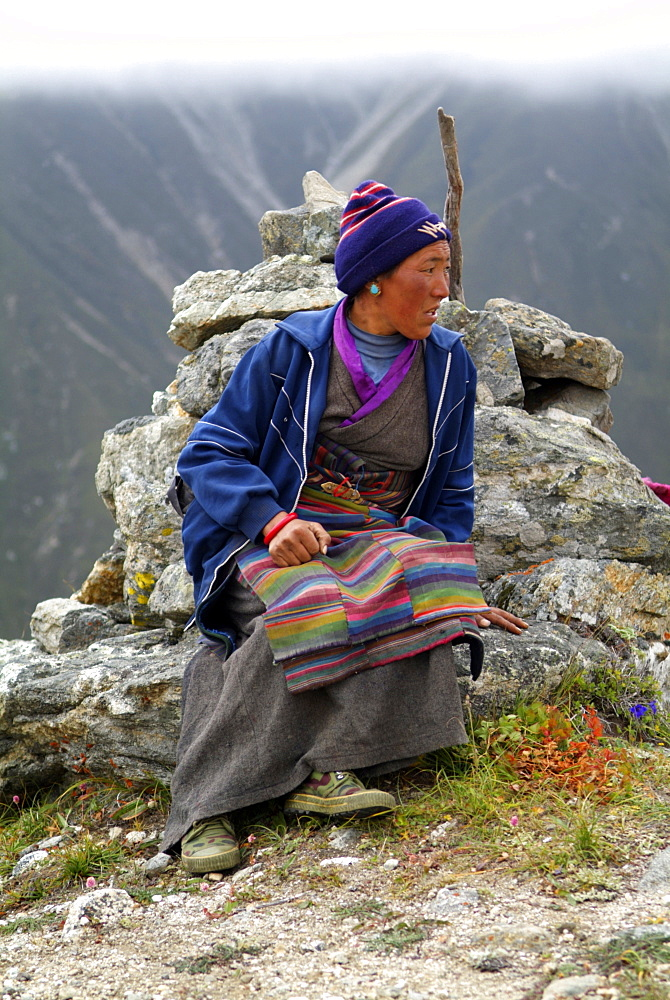 Tibetan Lady.  Mountain and Clouds.Traditional Dress,  Himalayas, Tibet. - 986-125