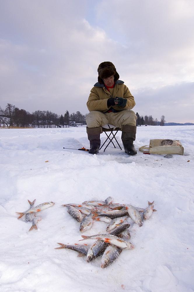 Ice fisherman on frozen Lake Puhajarv, Otepaa, Valgamaa, Estonia - 987-377
