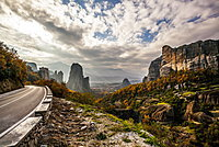 Landscape Of Rugged Cliffs, Road, Autumn Foliage And Monastery Rousanou In The Distance, Meteora, Greece
