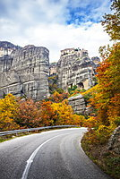 Monastery Perched On A Cliff, A Road And Autumn Foliage, Meteora, Greece