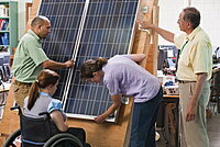 Engineering students examining photovoltaic panel's structural design and mounting