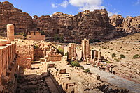 Camel train approaches Temenos Gateway with Qasr al-Bint temple, City of Petra ruins, Petra, UNESCO World Heritage Site, Jordan, Middle East