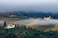 Castello di Gabbiano across a misty valley, church in foreground, San Casciano, Tuscany, Italy, Europe