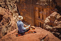Tourist with sun hat sits on carpet and looks from above into the gorge Siq, Pharaoh's treasure house carved into rock, facade of the treasure house Al-Khazneh, Khazne Faraun, mausoleum in the Nabataean city of Petra, near Wadi Musa, Jordan, Asia