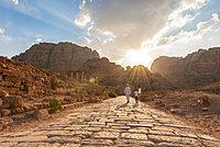 Two locals walk on Old Roman Road next to ruins of Petra, Nabataean city of Petra, near Wadi Musa, Jordan, Asia