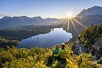 Two (hikers) looking at Eibsee lake at sunrise, sun shining over Bavarian alpine foothills, right Zugspitze, Wetterstein mountains near Grainau, Upper Bavaria, Bavaria, Germany, Europe
