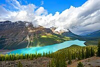 Cloudy mountain peaks, turquoise glacial lake surrounded by forest, Peyto Lake, Rocky Mountains, Banff National Park, Alberta Province, Canada, North America