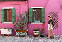 Young woman in front of colorful house, pink house facade, tourist on Burano island, Venice, Veneto, Italy, Europe