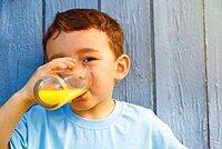 Child little boy drinking orange juice juice drinking glass, Germany, Europe