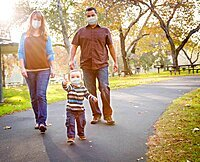 Happy Mixed Race Ethnic Family Walking In The Park Wearing Medical Face Mask, USA, North America