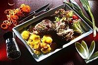 Steak prepared medium roasted cut with fried potatoes and salad