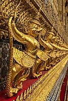 Golden sculptures of mythological creatures on wall at Wat Phra Kaew, Bangkok, Thailand