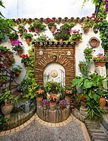 Fountain in the courtyard decorated with flowers, geraniums in flower pots on the house wall, Fiesta de los Patios, Cordoba, Andalusia, Spain, Europe