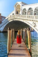 Young woman with red dress at a pier with boats, Grand Canal, Rialto Bridge, Venice, Veneto, Italy, Europe