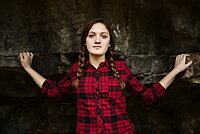 A girl standing in front of a rock wall looking at the camera, Toronto, Ontario, Canada
