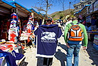 Tourists walk past souvenir tee shirt stating I have climbed up the The Great Wall, in Mutianyu, north of Beijing