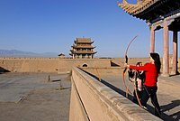 Chinese woman using a bow and arrow at the Jiayuguan Fortress with two gatehouses at the western end of the Great Wall of China, Silk Road, Gansu, China, Asia