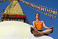 Young woman practicing yoga at Boudnanath stupa, showing the Padmasana pose, or Lotus pose, Kathmandu Valley, Kathmandu, Kathmandu District, Bagmati Zone, Nepal, Asia