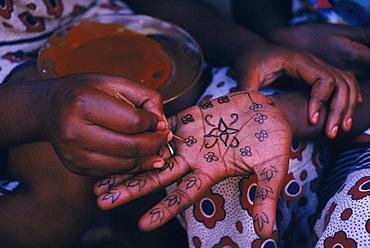 Lamu, Kenya. Swahili woman paints henna design on hand of a friend for Idd al Fitr festival.
