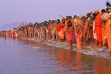 Having arrived at the confluence of the Yamuna and Ganges river for a purifying bath, these sadhus wait for their guru to enter the waters first. Kumbh mela festival: Allahabad India