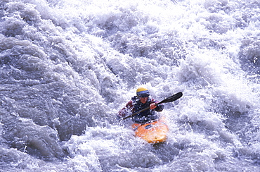 A kayaker makes her way through Class IV rapids outside of Queenstown on the South Island of New Zealand.