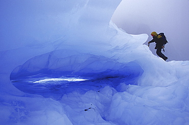 A climber makes his way past the opening to a small ice cave on the Franz Josef Glacier on New Zealand's South Island.