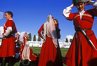 """Dancers from a traditional Abkhazian folkdance group adjust their costumes before a performance during a celebration on September 30, 2003 commemorating ten years of """"independence"""" from Georgia, in Sukhum, Abkhazia"""