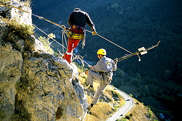 Working high above the busy road below, the two workers first secure the loose boulder to the cliff with a long metal pole.