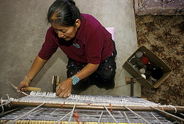 A Navajo woman weaves a rug in her home in Burnham, New Mexico on the Navajo Indian Reservation.