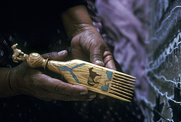 A Navajo weaver displays her handmade comb in her home in Burnham, New Mexico on the Navajo Indian Reservation.