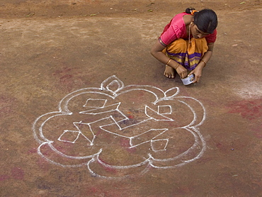 A woman performs the morning ritual of making a Rangoli, a Hindu religious decoration, outside her home in Hampi, Karnataka, India