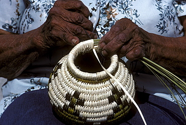 A Tohono O'Odham woman weaves a traditional basket in front of her house on the Tohono O'Odham Indian Reservation, Arizona