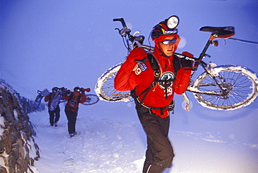 A man carries icy mountain bike through a snowstorm during the 2001 Adventure Racing World Championships in Switzerland, two other team members in the background