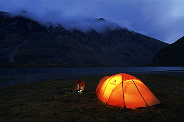 A man with a headlamp in front of a glowing tent on the shores of Russvatnet in Jotunheimen National Park, Norway.