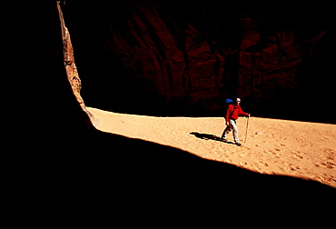Todd Snyder hikes in a slot canyon near Lake Powell, Utah. The walls of the canyon are sandstone cliffs and the path is sand.