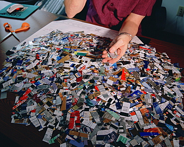 Credit card debt counselor Mary Rammel with a pile of credit cards cut up by debtors upon entering a credit counseling program in Willmington, DE, the credit card capital of the world. There are over 1.3 billion credit cards in America and in 2003 they accounted for over 786 billion dollars in credit card debt.