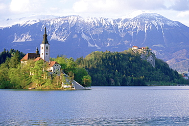 The Church of the Assumption and Bled Castle rise above Lake Bled, Slovenia, with the Kanmik-Savinja Alps rising in the background.