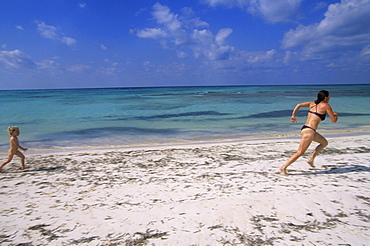 A little girl, Ruby Guy, chases her mother, Naomi Guy, on the white sand beach of Cayo Jutia, Pinar del Rio province, Cuba.  Cayo Jutia is a small island with uncrowded beaches that is popular with tourists and is part of the Las Colorados Archipelago in Western Cuba.
