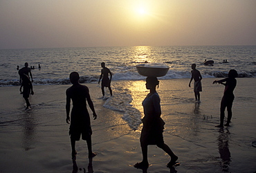 Locals walk and play on the beach at sunset on the Atlantic Coast of Gabon's capital, Libreville.