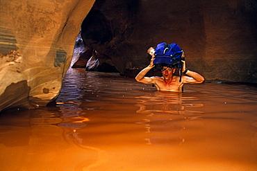 "Noel Jones canyoneering in ""The Black Hole"" of White Canyon, Cedar Mesa, Utah"