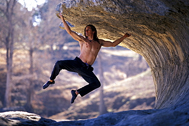 Jeff Jackson hangs on while bouldering on a steep limestone overhang outside of San Antonio, Texas.
