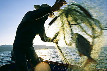 """Zen-ei Nakamura, an 88 year old fisherman form the town of Motobu, hauls up his catch from a net he had set earlier.  """"Fishing is my life"""" he said.  """"Ikigai"""" a Japanese word that roughly translated means """"reason for living"""", is something most elderly Okinawans have always had."""
